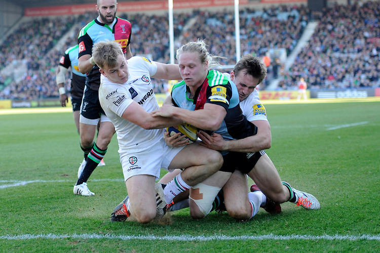 Matt Hopper of Harlequins scores a try despite the efforts of Scott Steele and Andrew Fenby of London Irish during the Aviva Premiership Rugby match between Harlequins and London Irish at The Twickenham Stoop on Saturday 7th March 2015 (Photo by Rob Munro)