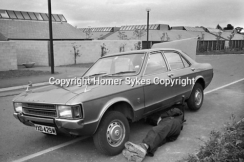 Milton Keynes, man working on his car at the side of the road. Buckinghamshire 1977 1970s