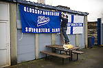 Glossop North End 0 Barnoldswick Town 1, 19/02/2011. Surrey Street, North West Counties League Premier Division. A supporter of Glossop North End hanging flags to a wall inside the club's Surrey Street ground before their home game with Barnoldswick Town in the Vodkat North West Counties League premier division. The visitors won the match by one goal to nil watched by a crowd of 203 spectators. Glossop North End celebrated their 125th anniversary in 2011 and were once members of the Football League in England, spending one season in the top division in 1899-00. Photo by Colin McPherson.