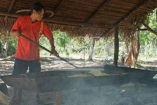Mato Grosso State, Brazil. Aldeia Metuktire (Kayapo). Man toasting manioc (cassava) flour in a steel pan over an open fire.