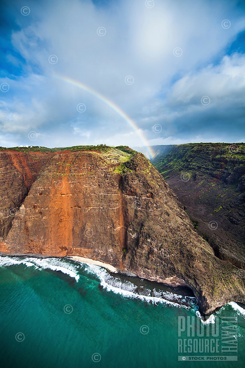 An aerial view of Na Pali coastline features a short stretch of beach and a big rainbow landing in a distant valley on Kaua'i.