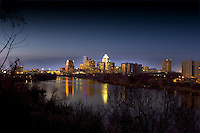 Austin, Texas downtown night city skyline with lights reflecting on the calm water of Townlake from Travis Heights hills in Austin, Texas.