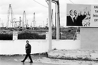 Azerbaijan. Baku Region. Baku. Balakhani. A man walks on the concrete road. A huge poster shows the current President of Azerbaijan, Ilham Aliyev (right) and his deceased father Heydar Aliyev (left). Ilham Aliyev also functions as the head of the New Azerbaijan Party. The deceased political leader Heydar Aliyev ( May 10, 1923 - December 12, 2003), also spelled as Heidar Aliev, Geidar Aliev, Haydar Aliyev. He was the president of Azerbaijan for the New Azerbaijan Party from June 1993 to October 2003. The State Oil Company of Azerbaijan Republic (SOCAR) is the project owner of the oil fields in Balakhani. Oil-extracting infrastructure.Drilling derricks and rigs. Spill and oil leakage from installation in operation. Oil production. Ecological disaster. Balakhani Oil Fields are a source of pollution as a result of well water and oil spill discharge. © 2007 Didier Ruef