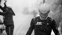 Milan - San Remo 2013: the iced edition.Adam Hansen (AUS) walking up to the teambus to get warm while the mechanics hurry to get all the bikes ready for a 2nd start 50km away