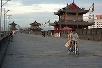 Couple riding a bicycle along the ramparts of the South Gate Pavilion, Xian, Shaanxi, China.