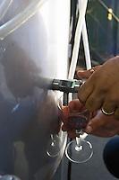 Petrit Cobo taking a sample from a stainless steel fermentation vat. Cobo winery, Poshnje, Berat. Albania, Balkan, Europe.