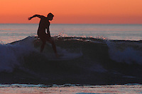 Pacific Beach, San Diego, California, USA:  Monday, January 19 2009.  A surfer enjoys a wave at the bottom of Loring Street just after sunset.  The Martin Luther King Jnr Day holiday was marked by warm weather, big surf and a technicolored sunset as much of the rest of the country shivered in the cold.