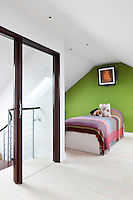 A child's bedroom in an attic room. A single bed is placed against a green painted wall and has a red check pattern bedcover. A full height glass door stands at the top of the stairs.