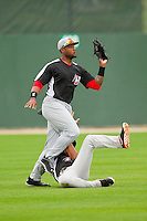 Hickory Crawdads left fielder Jordan Akins (5) catches a fly ball as center fielder Nick Williams (1) slides into his legs during the game against the Kannapolis Intimidators at CMC-Northeast Stadium on April 14, 2013 in Kannapolis, North Carolina.  The Intimidators defeated the Crawdads 6-0.  (Brian Westerholt/Four Seam Images)