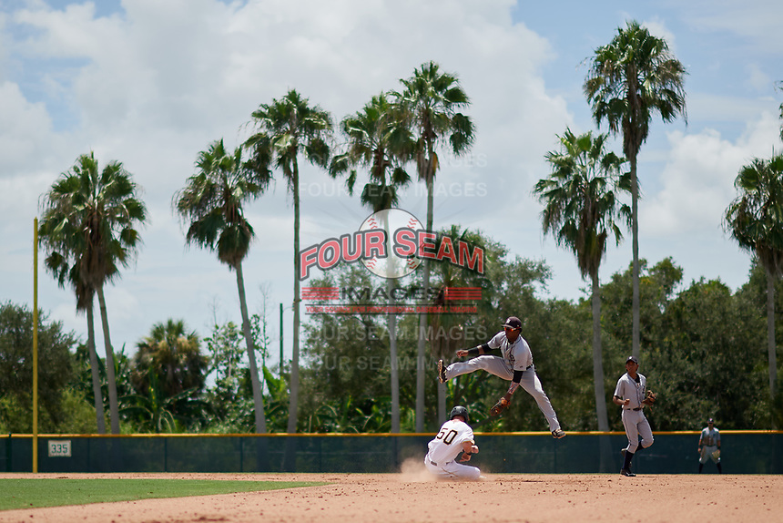 GCL Tigers West second baseman Hector Martinez (4) tries to apply a swipe tag as GCL Pirates Patrick Dorrian (50) slides into second base during a game against the GCL Pirates on August 13, 2018 at Pirate City Complex in Bradenton, Florida.  GCL Tigers West defeated GCL Pirates 5-1.  (Mike Janes/Four Seam Images)