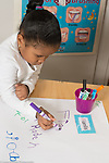 Education Preschool 4 year olds start of day sign in girl writing letters of her name, using name card as a guide