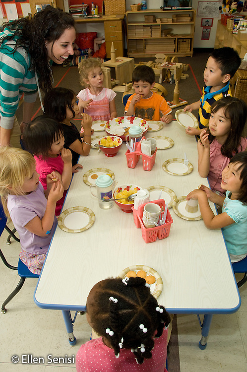 MR / College Park, Maryland.Center for Young Children, laboratory school within the College of Education at the University of Maryland. Full day developmental program of early childhood education for children of faculty, staff, and students at the university..Teacher and students talk and eat at a table during snack time. .MR: AH-gPcyc.© Ellen B. Senisi