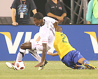 Edson Buddle #14 of the USA falls after a tackle from Daniel Alves #2 of Brazil during an international friendly matchl in Giants Stadium, on August 10 2010, in East Rutherford, New Jersey.Brazil won 2-0.