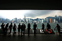 A line of visitors viewing the iconic skyline of Hong Kong island on the other side harbor front in Tsim Sha Tsui. .