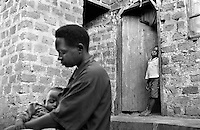 A young boy watches his oldest sister, who is now head of the family in Kampala, Uganda on April 20, 2001. More than 13 million African children have been orphaned by the the AIDS pandemic. Worldwide, more than 20 million people have died since the first cases of AIDS were identified in 1981.