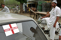 Sticker supporting the England football team on the rear window of a car in the town of Wesa, on the Grand Trunk Road near Attock in Pakistan. This area developed as a major area for migration as a result of its boat trade along the Indus River, which developed into a seafaring tradition. In the background a horse pulls a cart.