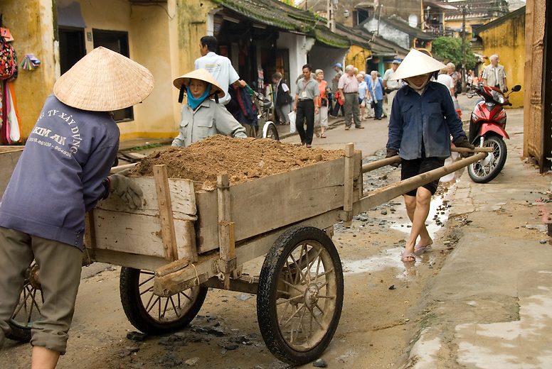 Three woman work to repair streets in Hoi An, Vietnam.  Young women take on many traditionally male dominated tasks and jobs in vietnam such as fixing motorbikes and repairing roads.