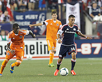 New England Revolution midfielder Diego Fagundez (14) prepares to pass as Houston Dynamo defender Kofi Sarkodie (8) closes. In a Major League Soccer (MLS) match, Houston Dynamo (orange) defeated the New England Revolution (blue), 2-1, at Gillette Stadium on July 13, 2013.