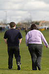 Overweight fat young couple. Rear view  South London SE21 London UK 2008.