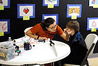 Marc Hayot/Siloam Sunday. Libby Pratt paints the face of a young member at the Boys and Girls Club's Halloween party.