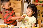 Preschool ages 3-5 art activity play dough boy offering girl a lump of play dough sharing horizontal