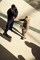 Man and woman conducting business; shaking hands. High view. Professionals. Lawyers. Businesswoman. Businessman. Denver Colorado USA.