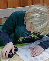 Kinder basteln ein Fensterbild mit Blüten, Junge locht die Ecken des Pergamentpapiers