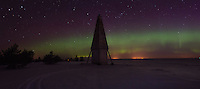 The Northern Lights backlight Keskiniemi Daybeacon on the northern shore of Hailuoto Island which is located in the Gulf off Bothnia off Oulu, Finland. Photo taken in April at 2:00 am.