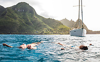 A couple enjoy the warm waters off their anchored sailboat on the Na Pali Coast of Kaua'i.