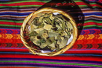 Peru, Cusco.  Bowl of Coca Leaves sitting on Quechua fabric.  Tea from coca helps reduce effects of Cusco's 11,000-foot altitude.