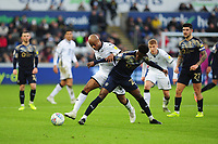 Andre Ayew of Swansea City vies for possession with Clarke Oduor of Barnsley during the Sky Bet Championship match between Swansea City and Barnsley at the Liberty Stadium in Swansea, Wales, UK. Sunday 29 December 2019