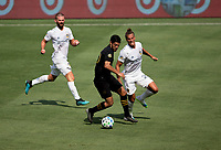 LOS ANGELES, CA - AUGUST 22: Carlos Vela #10 of LAFC attempts to move past Rolf Feltscher #25  of the Los Angeles Galaxy during a game between Los Angeles Galaxy and Los Angeles FC at Banc of California Stadium on August 22, 2020 in Los Angeles, California.