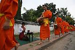 Ceremonie des offrandes aux moines des monasteres de la ville de Luang Prabang. A l'aube, les habitants donnent du riz aux moines passant dans la rue. Laos
