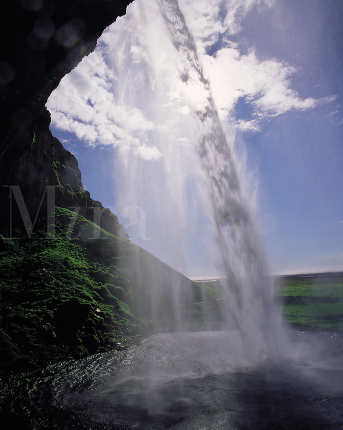 Looking out through the falling water of the Seljalandfoss waterfall, southern Icelan