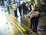 """© Joel Goodman - 07973 332324 . NO SYNDICATION PERMITTED . 20/12/2014 . Manchester , UK . A woman vomits in to a gutter on Deansgate , as a man comforts her . """" Mad Friday """" revellers out in the rain and cold in Manchester . Mad Friday is typically the busiest day of the year for emergency services , taking place on the last Friday before Christmas when office Christmas parties and Christmas revellers enjoy a night out .  Photo credit : Joel Goodman"""