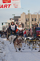 Musher Bruce Linton and Iditarider Bradley Belcher.leave the 2011 Iditarod ceremonial start line in downtown Anchorage, Alaska
