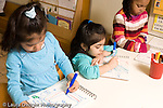 Preschool Headstart 3-5 year olds art activity row of three girls drawing with marker one using left hand and the other two using right hand horizontal