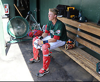 Catcher Jordan Weems (15) of the Greenville Drive takes a breather in front of the fan in the dugout during a game against the Lexington Legends on April 5, 2012, at Fluor Field at the West End in Greenville, South Carolina. Weems was a third-round pick by the Boston Red Sox in the 2011 First-Year Player Draft. (Tom Priddy/Four Seam Images)