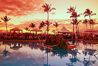 People gathering, under a vivid golden sunset, amid palm trees, cabanas, an outrigger canoe filled with flowers and reflections in a pool at Kapalua, Maui.