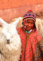 An Peruvian boy of Incan decent in traditional attire of serape and patterned hat, poses with his lama. Cuzco, Peru.