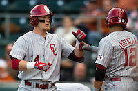 Oklahoma Sooners first basman Matt Oberste #14 is greeted by teammate Matt Lorenzana #12 after scoring against the Texas Longhorns in the NCAA baseball game on April 5, 2013 at UFCU DischFalk Field in Austin Texas. Oklahoma defeated Texas 2-1. (Andrew Woolley/Four Seam Images).