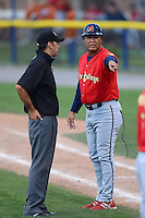 State College Spikes coach Ramon Ortiz (35) argues a call with umpire Nate Caldwell during a game against the Batavia Muckdogs on July 28, 2013 at Dwyer Stadium in Batavia, New York.  Batavia defeated State College 10-5.  (Mike Janes/Four Seam Images)