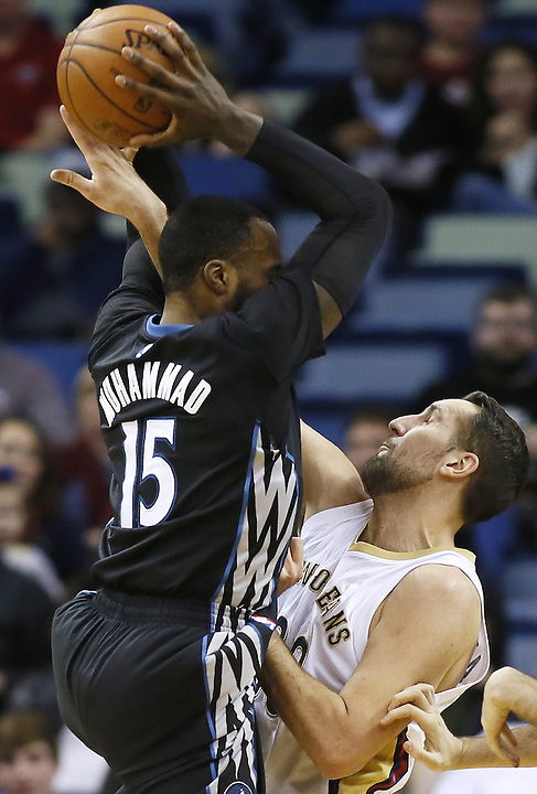 Minnesota Timberwolves forward Shabazz Muhammad (15) rebounds the ball over New Orleans Pelicans forward Ryan Anderson (33) during the first half of an NBA basketball game Tuesday, Jan. 19, 2016, in New Orleans. (AP Photo/Jonathan Bachman)