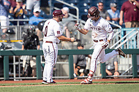 Mississippi State Bulldogs third baseman Marshall Gilbert (34) celebrates with third base coach Kyle Cheesebrough (0) after hitting a home run during Game 8 of the NCAA College World Series against the Vanderbilt Commodores on June 19, 2019 at TD Ameritrade Park in Omaha, Nebraska. Vanderbilt defeated Mississippi State 6-3. (Andrew Woolley/Four Seam Images)