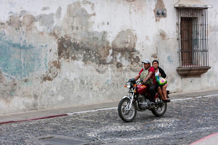Antigua, Guatemala.  Couple on Motorbike, Passenger no Helmet.