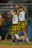 Savannah Bananas Nick Clarno (15) and Alex Degan (35) celebrate a hit during a Coastal Plain League game against the Macon Bacon on July 15, 2020 at Grayson Stadium in Savannah, Georgia.  Savannah wore kilts for their St. Patrick's Day in July promotion.  (Mike Janes/Four Seam Images)