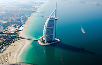Worlds only 7 star hotel in Dubai UAE called the Burj Al Arab from helicopter above aerial with luxury and water  at beach in United Arab Emirates