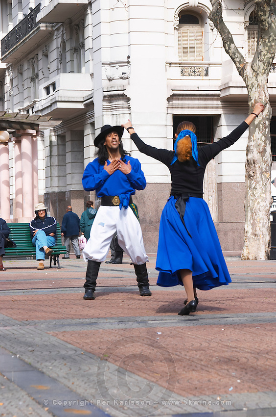Plaza de Cagancha Square, a couple man and woman dancing flamenco and tango on a city square, dressed in blue skirt black top, white pants, blue shirt and black hat. Man gesturing passion and love and the woman holding out her arms in welcome. Montevideo, Uruguay, South America