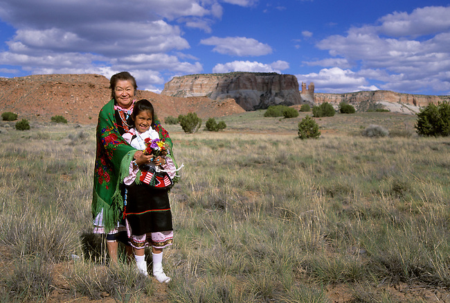 Native American family of a Zuni grandmother dressed in traditional clothing and floral shawl puts her arms around her elementary school age grand-daughter with sacred Corn Mountain in the background, Zuni Pueblo, New Mexico