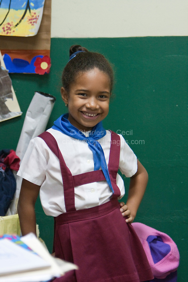 Cuba, Havana.  Girl in Primary School Classroom.  Red and white are the colors for primary school uniforms.